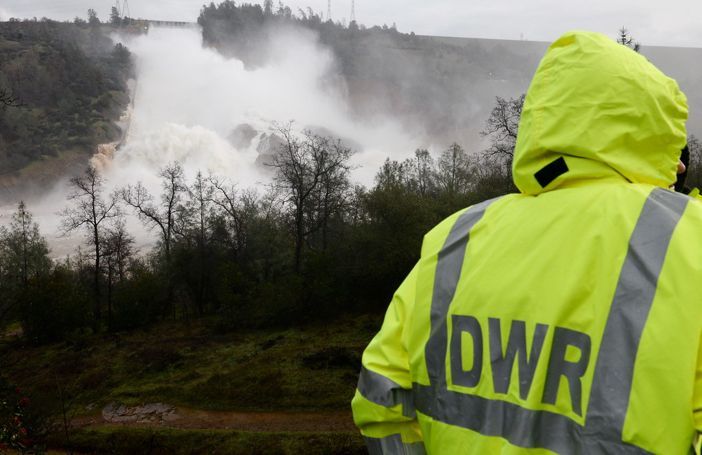 . Media representatives, law enforcement and DWR employees are on scene along Oro Dam Blvd. East watching approx. 65,000 cfs of water flow down the damaged Lake Oroville Dam Spillway Friday Feb. 10, 2017. (Bill Husa -- Enterprise-Record)