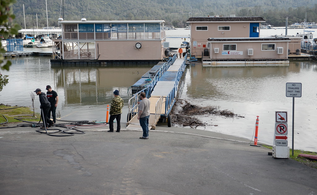 . Bidwell Canyon Marina employees keep up with moving the docks to accomodate the rising water as approx. 65,000 cfs flows down the damaged Lake Oroville Dam Spillway Friday Feb. 10, 2017. (Bill Husa -- Enterprise-Record)