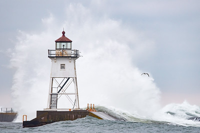 "SUPERIOR WAVES 6148  ""Ka-BOOM!""  A large wave explodes into the air behind the Grand Marais lighthouse on January 5, 2016 - Grand Marais, MN"