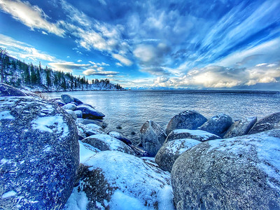 Lake Tahoe East Shore view of lake with snow covered rocks in the foreground. Lake Tahoe Nevada