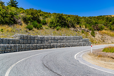 Retention wall on the road, Southern Alps , Ka tiritiri o te Moana,  just outside  Queenstown, Otago, South Island, New Zealand, on the way to Wanaka on a crazy beautiful sky day