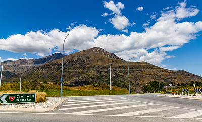 Road junction, signage, Southern Alps , Ka tiritiri o te Moana,  just outside  Queenstown, Otago, South Island, New Zealand, on the way to Wanaka on a crazy beautiful sky day