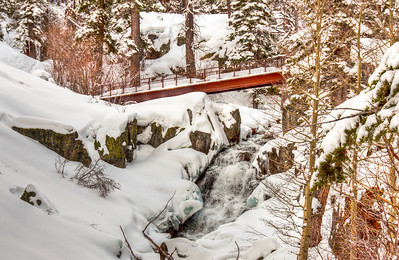 snowy-forest-stream-bridge