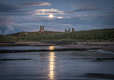 Dunstanburgh castle under a full moon.