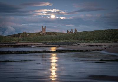 Dunstanburgh castle under a full moon.