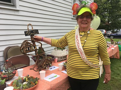 Lynne Martin stands with the many fairy gardens up for auction
