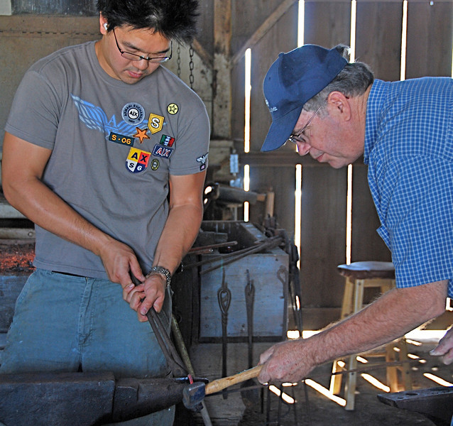 Two two blacksmith workers team in forging something or other.