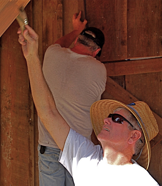 Skip McCowan applying semi-transparent stain to post of rehabbed barn we all worked on.
