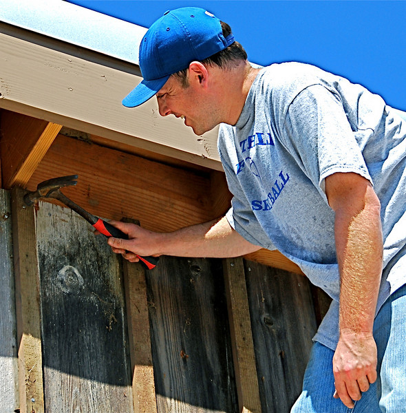 Red-badger Dan Garfin pounds nail into batten affixed between boards on refurbished and enlarged barn at Rush Ranch.