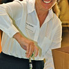 Volunteer Lisa Shaffer, with Prudential California Realty in Orinda, opens a bottle of Champagne.