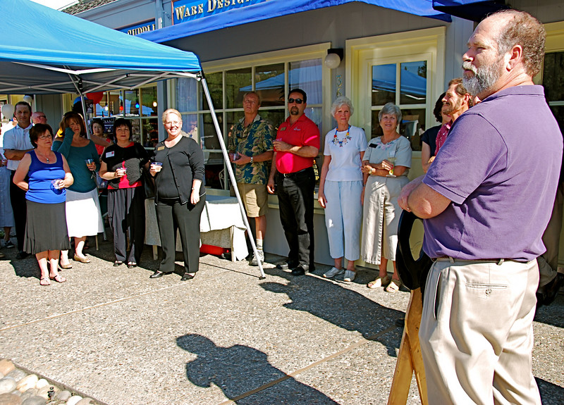 Having just cut the official ceremonial ribbon in front of his newly relocated store in Happy Valley Plaza on Mt. Diablo Blvd., owner Steve Ware addresses invitees, clustered under an awning to screen them from sweltering heat.