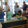 Steve Ware (purple shirt at window) chats with one of the many guests who attended grand-opening ceremonies July 16 for Ware Designs jewelry store. relocated from the east side of Lafayette to new quarters on Mt. Diablo Blvd. between the post office and Trader Joe's. At far left is Ware's wife Laurie.