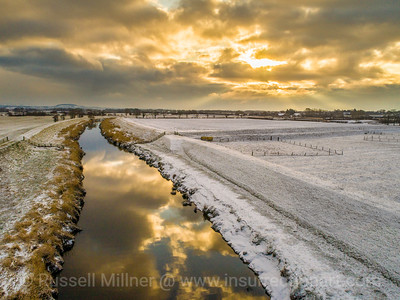 Sun rises over the snowy fields and the River Wyre, Great Eccleston, England