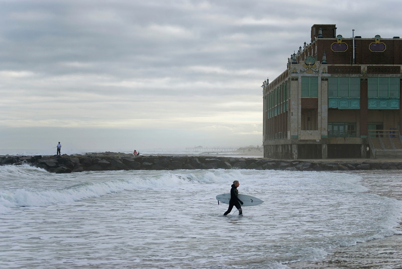 A surfer in a wetsuit exits the ocean near the casino on this November day in Asbury Park, New Jersey.