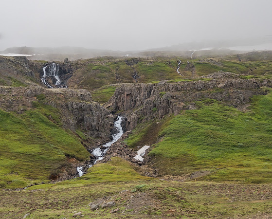 Roadside scenery in Iceland, where waterfalls emerge from glaciers on foggy mountaintops and tumble through the rocky landscape