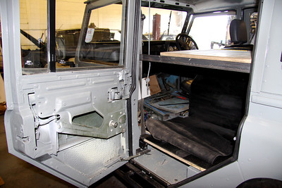 Area behind passenger seat where jerry cans of water will be stored. Sleeping platform above folds open to allow better access to jerry cans. Leisure battery may also be fitted in this space.