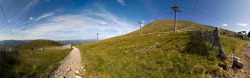 25.07.2011, Schottland, Torlundy, in den Highlands noerdlich von  Fort William. Eine Kabinen-Seilbahn der -Nevis Range Mountain Experience- fuehrt  zur 650m hoch gelegenen Bergstation auf die Flanke des Berges -Aonach Mor- in der Ben Nevis- Gebirgsregion. Ein Wanderweg an der Flanke des Berges. Panoramaaufnahme.