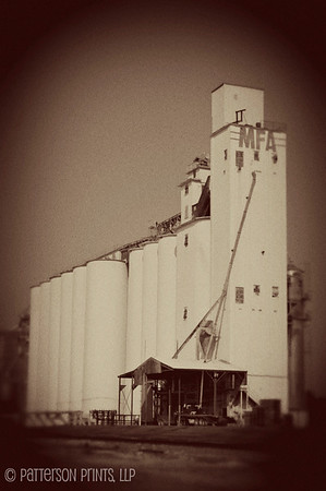 "Center of Commerce - Higginsville, MO has been a farming community since its founding by Harvey Higgins back in 1869, and at one time was considered the ""Seed Corn Capitol of the World"".  The MFA grain elevator located on the rail line now owned by Union Pacific is still used to ship much of the grain grown in the area."