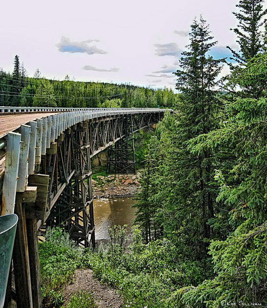 "Kiskatinaw Bridge, Old Alaska Highway.  Built in 1942-43 (as part of the Alaska Highway construction) by the US Army Corp of Engineers, this bridge is the last wooden bridge still in use that was built by the Corp, and was the first of it's kind in Canada.   It is constructed completely of timber except for cement footings, and curves 9 degrees over it's 534 foot length.<br /> <br /> Today the highway has been straightened and the bridge replaced, but one can follow signs off the official highway back to the ""Old Alaska Highway"" and drive over the bridge.  The is a provincial park along the river under the bridge with camping and picnic facilities."