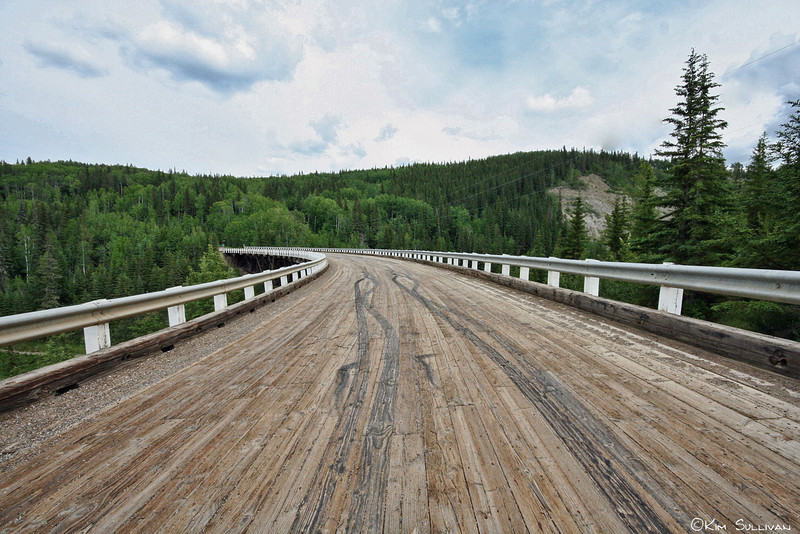 "Looking across the Kiskatinaw Bridge, Old Alaska Highway.  Built in 1942-43 (as part of the Alaska Highway construction) by the US Army Corp of Engineers, this bridge is the last wooden bridge still in use that was built by the Corp, and was the first of it's kind in Canada.   It is constructed completely of timber except for cement footings, and curves 9 degrees over it's 534 foot length.<br /> <br /> Today the highway has been straightened and the bridge replaced, but one can follow signs off the official highway back to the ""Old Alaska Highway"" and drive over the bridge.  The is a provincial park along the river under the bridge with camping and picnic facilities."