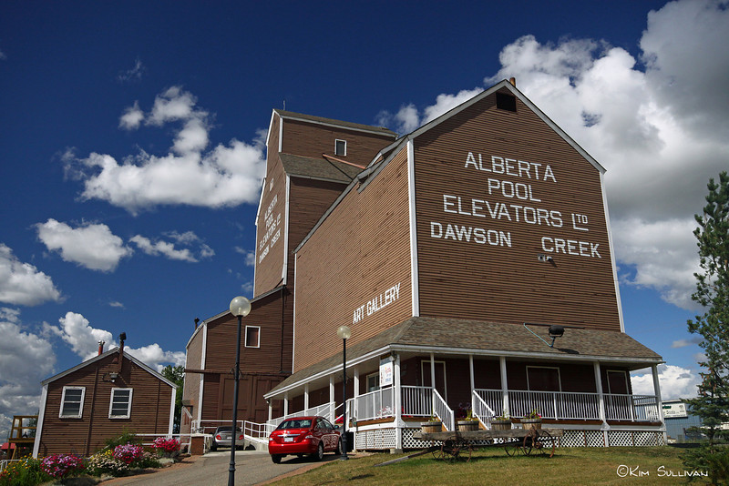 "Art Gallery, Dawson Creek BC<br /> <br /> In 1947 Dawson Creek was the largest grain producer in the British Empire, and by 1950 8 grain elevators lined up along the Alaska Highway. This one was built by the Alberta Wheat Pool in 1948. However, by 1980 6 of the elevators had been replaced by modern concrete ones, and all across the prairies the wooden structures that had stood for 100 years were disappearing. The Alberta Wheat Pool sold ""Elevator #2"" to the city of Dawson Creek for $1.00, and it was moved to it's present location. The Art Gallery opened in 1983"
