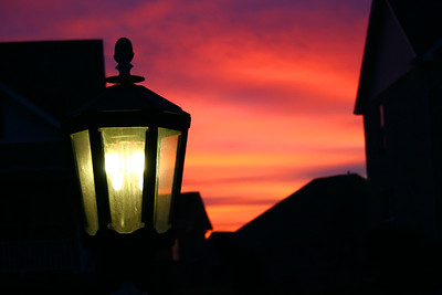 Lonely gas lamp against a crimson sky