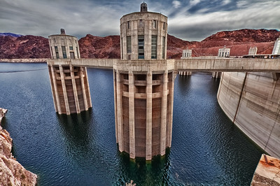 The intake towers are four reinforced-concrete structures located above the dam, two on each side of the canyon. The diameter of these towers is 82 feet at the base, 63 feet 3 inches at the top, and 29 feet 8 inches inside. Each tower is 395 feet high and each controls one-fourth the supply of water for the powerplant turbines. The four towers contain 93,674 cubic yards of concrete and 15,299,604 pounds of steel.