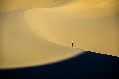 Dune Ridges and shadows converge near a lone hiker.