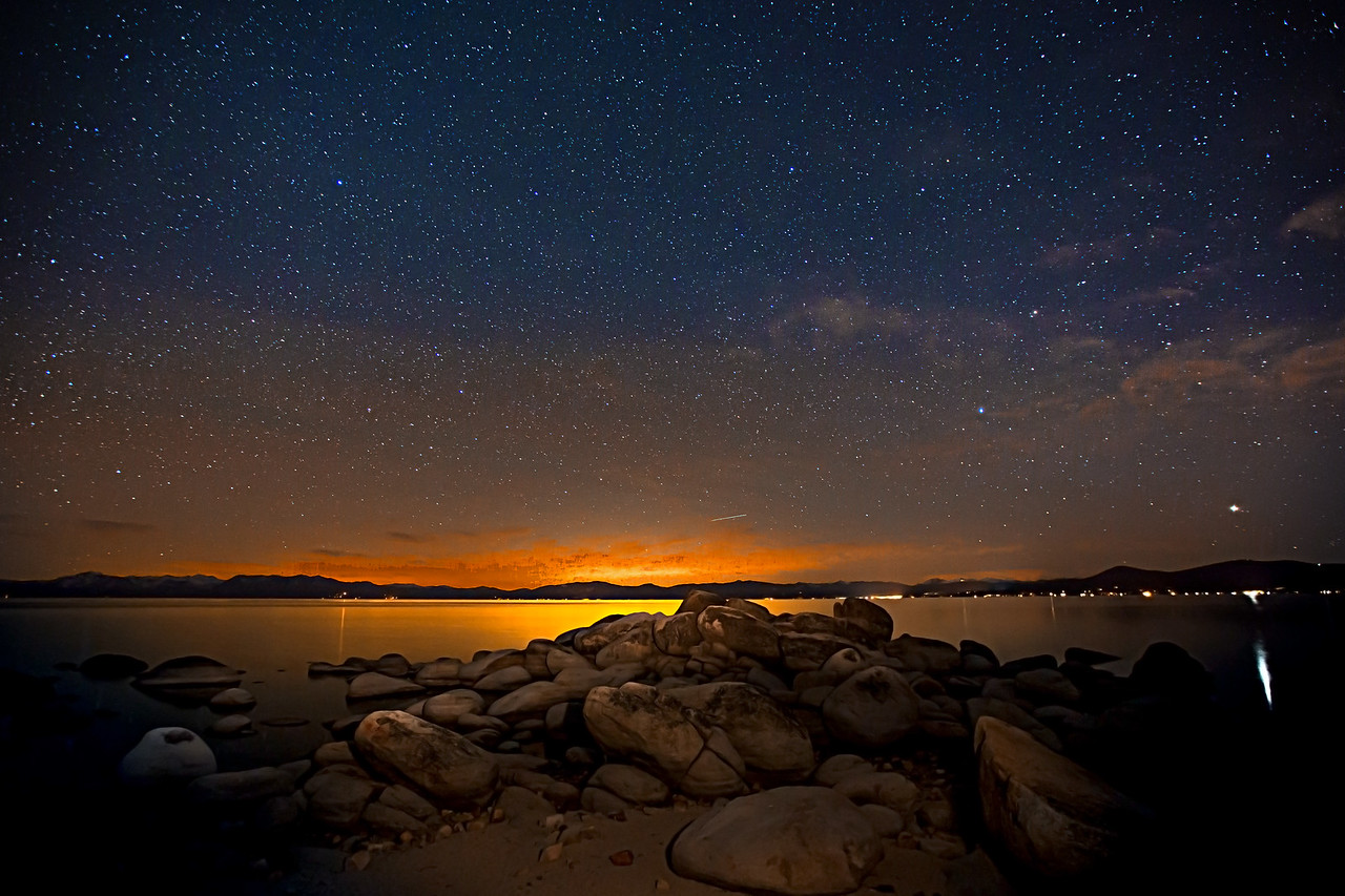 The stillness of Lake Tahoe with the glow from the lights of Sacramento over the mountains in the distance.