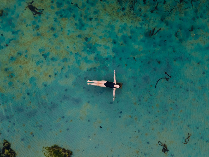 Aerial view of woman swimming in Glencairn tidal pool, Cape Town, South Africa.