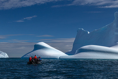 A small boat explores Icebergs worn smooth by wind and waves in Antarctica.