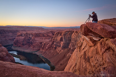 A photographer sets up close to the edge at Horseshoe Bend.