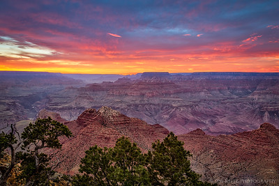 The clouds in the sky light up just after the sun disappears below the horizon. Grand Canyon National Park.