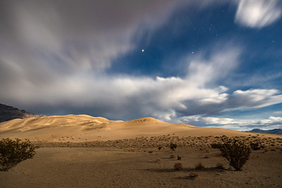 Moonlight on Eureka Dunes. A break in the clouds allows the moon to briefly illuminate the dunes & let some stars shine through.