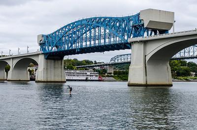 A SUP racer crosses under the John Ross Bridge