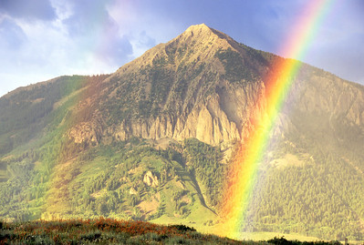 A beautiful rainbow touches down on a hillside just above the town of Crested Butte