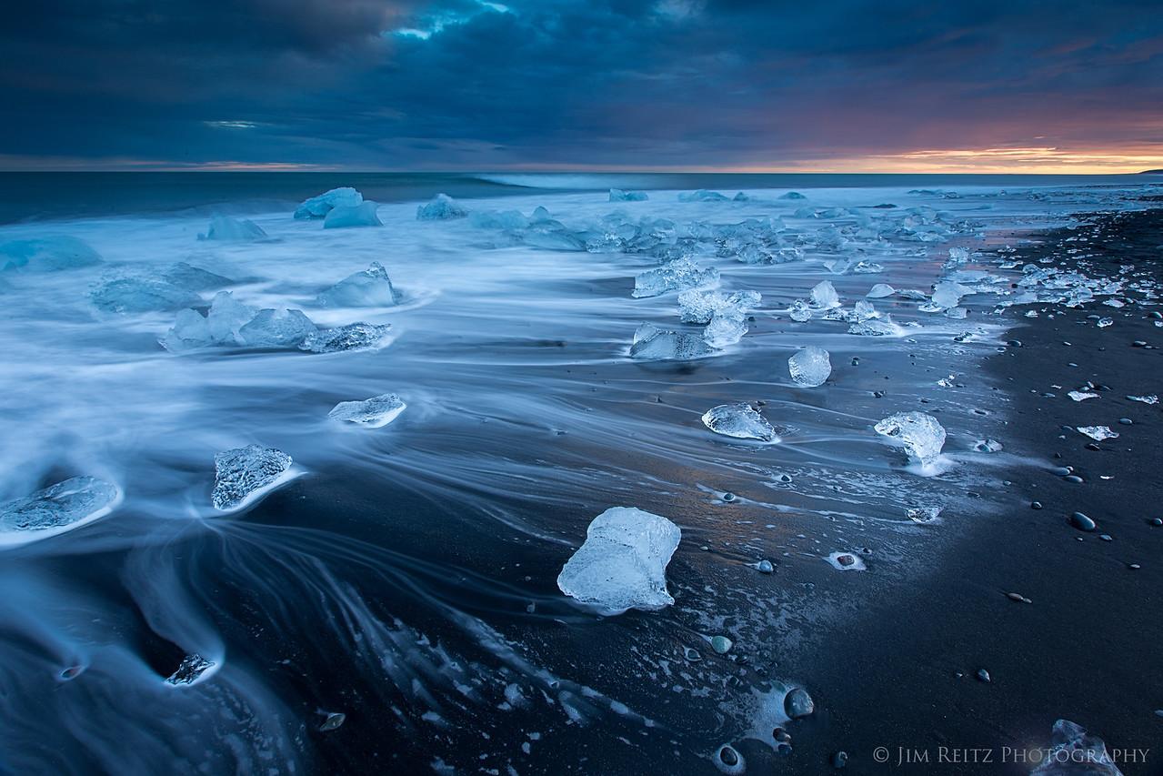 Icebergs wash up on black sand at the beach near Jökulsárlón glacier lagoon, in eastern Iceland.