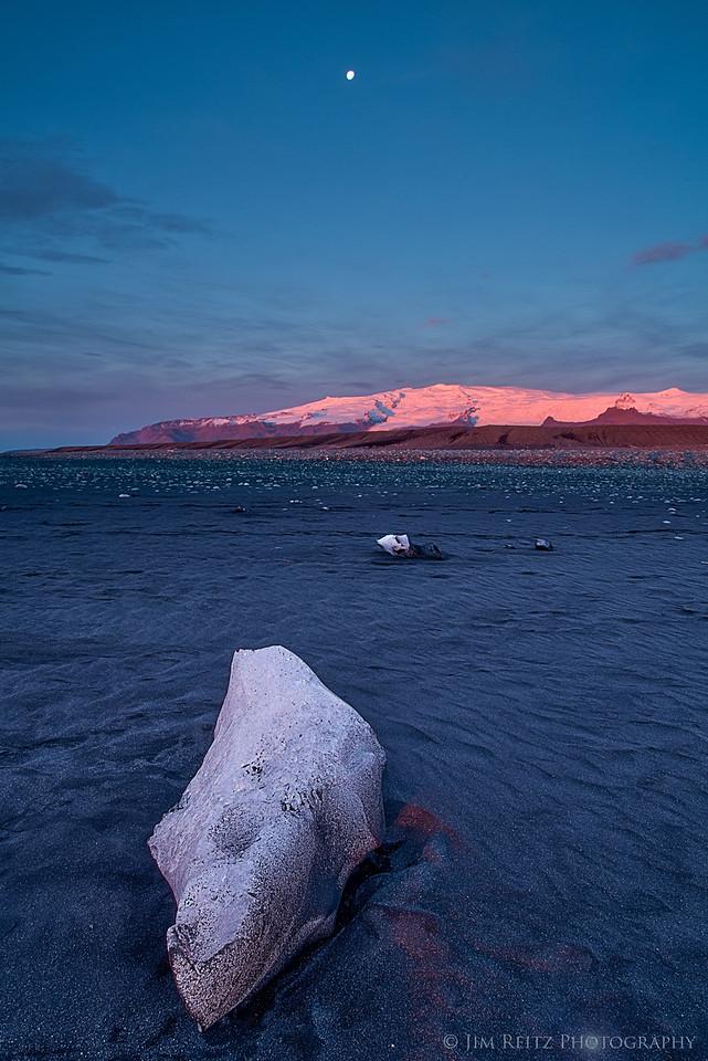 Moon, alpenglow on distant glaciers, and melting icebergs on black sand. Near Jökulsárlón, eastern Iceland.