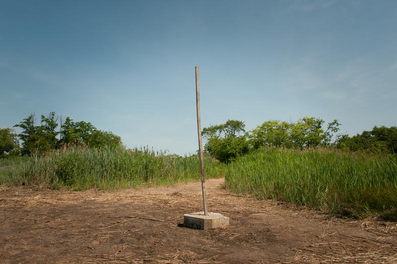 Wooden pole set in concrete block