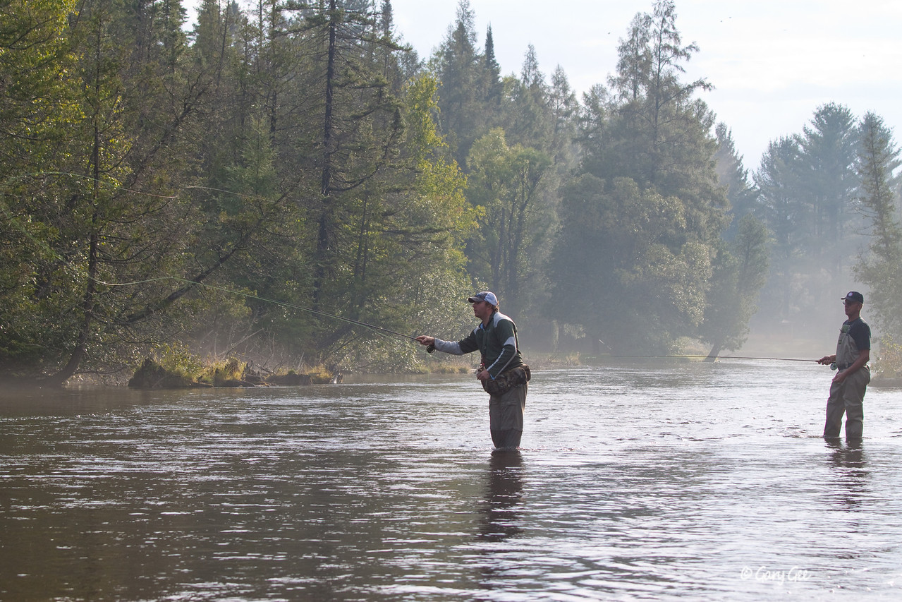 Fisherman on the Au Sable River as the morning fog clears in the background...