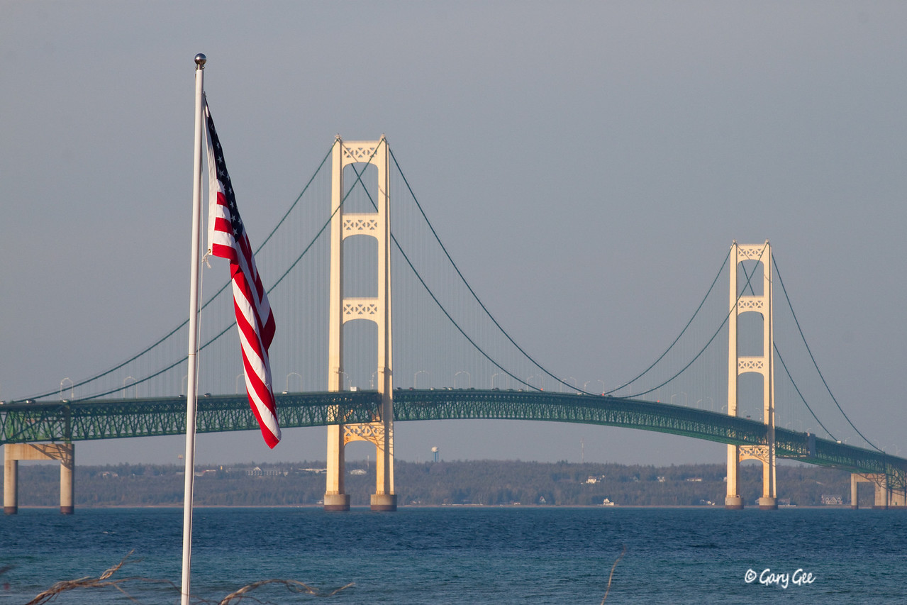 The Mackinac Bridge with an American flag in the foreground