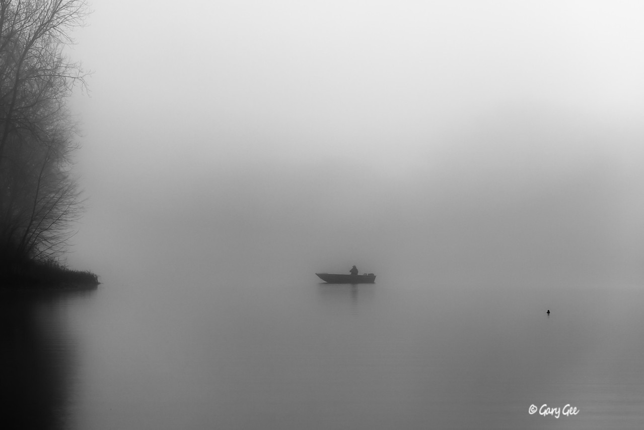 Lonely fisherman in the fog with nearby duck