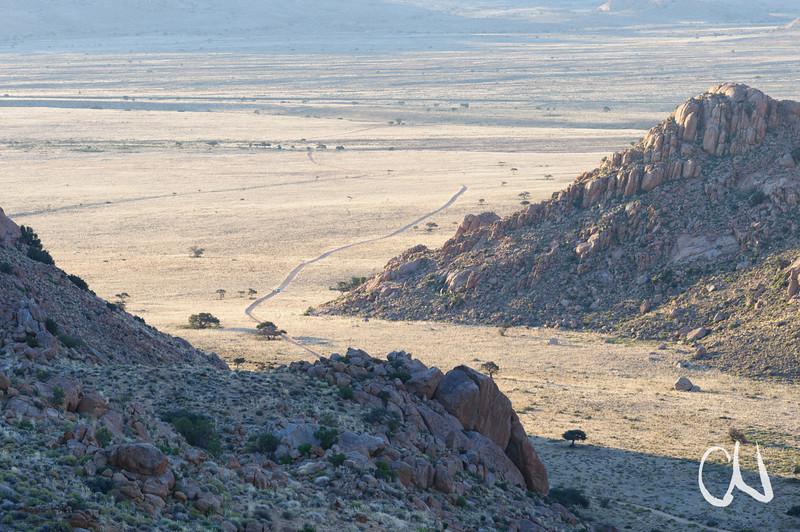 Straße zwischen Grasland und Felsen, Klein Aus Vista, Namibia