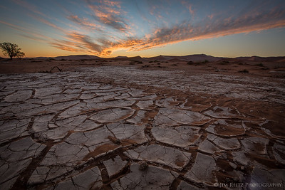 Craked, dried mud in the seasonal riverbed of Sossusvlei, Namibia - at sunset.