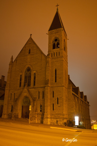 Catholic Church time exposure after dark in the fog on a steep street-side of Burlington, Iowa