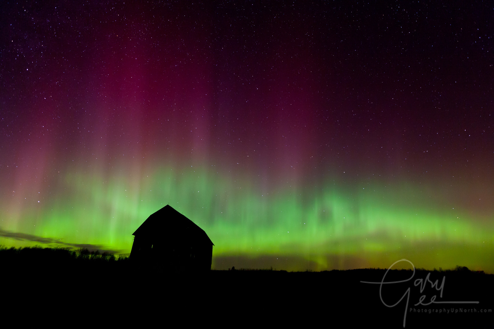 Brilliant display of Northern Lights with old barn in Michigan.
