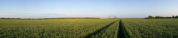 11.06.2011, Insel Fehmarn, die Fehmarn-Sund-Bruecke bei Strukkamphuk, Panorama-Aufnahme.Wikipedia: Die Fehmarnsundbrücke verbindet die Insel Fehmarn in der Ostsee mit dem Festland bei Großenbrode.Die 963 Meter lange kombinierte Straßen- und Eisenbahnbrücke überspannt den 1300 Meter breiten Fehmarnsund, wobei die restlichen 337 Meter aus beidseitigen Rampen bestehen. Sie hat eine lichte Höhe von 23 Metern über dem Mittelwasser und bietet für den Schiffsverkehr einen Durchgang von 240 Metern Breite sowie eine Durchfahrtshöhe von 23 Metern über NN. Sie ist eine Stahlkonstruktion mit 21 Metern Breite, von denen sechs Meter von der Deutschen Bahn genutzt werden. Der zirka 268,5 Meter lange Bogen hat eine Stützweite von 248 Metern und ist mit 45 Metern über der Fahrbahn höchster Punkt.Die Netzwerkbogenbrücke wurde von den Ingenieuren G. Fischer, T. Jahnke und P. Stein der Gutehoffnungshütte Sterkrade AG, Oberhausen-Sterkrade entworfen. Bei der architektonischen Gestaltung wirkte der Architekt Gerd Lohmer mit. Die Brücke wurde am 30. April 1963 eingeweiht. Gleichzeitig wurde die Fährlinie von Großenbrode Kai nach Gedser durch die Fährlinie Puttgarden–Rødby (Dänemark) ersetzt.Durch die Fehmarnsundbrücke und den gleichzeitig gebauten Fährhafen Puttgarden auf Fehmarn wurde die durchschnittliche Reisezeit auf der so genannten Vogelfluglinie von Hamburg nach Kopenhagen deutlich verkürzt.Seit 1999 steht die Fehmarnsundbrücke auf Vorschlag des Landesamtes für Denkmalschutz in Kiel unter Denkmalschutz und ist mittlerweile zum Wahrzeichen von Fehmarn und Schleswig-Holstein geworden.