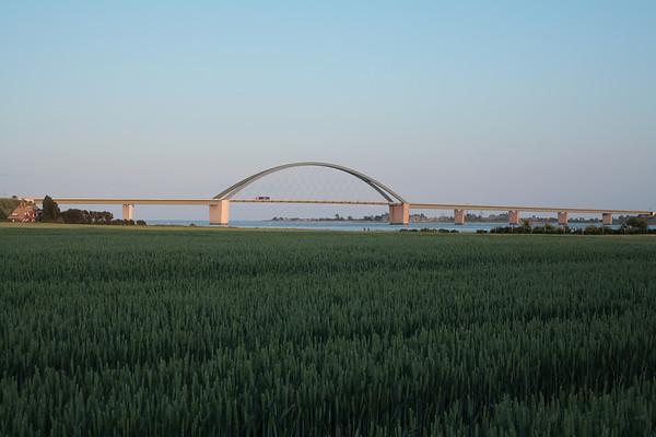 11.06.2011, Insel Fehmarn, die Fehmarn-Sund-Bruecke bei Strukkamphuk. Wikipedia: Die Fehmarnsundbrücke verbindet die Insel Fehmarn in der Ostsee mit dem Festland bei Großenbrode.Die 963 Meter lange kombinierte Straßen- und Eisenbahnbrücke überspannt den 1300 Meter breiten Fehmarnsund, wobei die restlichen 337 Meter aus beidseitigen Rampen bestehen. Sie hat eine lichte Höhe von 23 Metern über dem Mittelwasser und bietet für den Schiffsverkehr einen Durchgang von 240 Metern Breite sowie eine Durchfahrtshöhe von 23 Metern über NN. Sie ist eine Stahlkonstruktion mit 21 Metern Breite, von denen sechs Meter von der Deutschen Bahn genutzt werden. Der zirka 268,5 Meter lange Bogen hat eine Stützweite von 248 Metern und ist mit 45 Metern über der Fahrbahn höchster Punkt.Die Netzwerkbogenbrücke wurde von den Ingenieuren G. Fischer, T. Jahnke und P. Stein der Gutehoffnungshütte Sterkrade AG, Oberhausen-Sterkrade entworfen. Bei der architektonischen Gestaltung wirkte der Architekt Gerd Lohmer mit. Die Brücke wurde am 30. April 1963 eingeweiht. Gleichzeitig wurde die Fährlinie von Großenbrode Kai nach Gedser durch die Fährlinie Puttgarden–Rødby (Dänemark) ersetzt.Durch die Fehmarnsundbrücke und den gleichzeitig gebauten Fährhafen Puttgarden auf Fehmarn wurde die durchschnittliche Reisezeit auf der so genannten Vogelfluglinie von Hamburg nach Kopenhagen deutlich verkürzt.Seit 1999 steht die Fehmarnsundbrücke auf Vorschlag des Landesamtes für Denkmalschutz in Kiel unter Denkmalschutz und ist mittlerweile zum Wahrzeichen von Fehmarn und Schleswig-Holstein geworden.