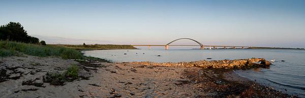 11.06.2011, Insel Fehmarn, die Fehmarn-Sund-Bruecke bei Strukkamphuk, Abendstimmung, Panorama-Aufnahme.Wikipedia: Die Fehmarnsundbrücke verbindet die Insel Fehmarn in der Ostsee mit dem Festland bei Großenbrode.Die 963 Meter lange kombinierte Straßen- und Eisenbahnbrücke überspannt den 1300 Meter breiten Fehmarnsund, wobei die restlichen 337 Meter aus beidseitigen Rampen bestehen. Sie hat eine lichte Höhe von 23 Metern über dem Mittelwasser und bietet für den Schiffsverkehr einen Durchgang von 240 Metern Breite sowie eine Durchfahrtshöhe von 23 Metern über NN. Sie ist eine Stahlkonstruktion mit 21 Metern Breite, von denen sechs Meter von der Deutschen Bahn genutzt werden. Der zirka 268,5 Meter lange Bogen hat eine Stützweite von 248 Metern und ist mit 45 Metern über der Fahrbahn höchster Punkt.Die Netzwerkbogenbrücke wurde von den Ingenieuren G. Fischer, T. Jahnke und P. Stein der Gutehoffnungshütte Sterkrade AG, Oberhausen-Sterkrade entworfen. Bei der architektonischen Gestaltung wirkte der Architekt Gerd Lohmer mit. Die Brücke wurde am 30. April 1963 eingeweiht. Gleichzeitig wurde die Fährlinie von Großenbrode Kai nach Gedser durch die Fährlinie Puttgarden–Rødby (Dänemark) ersetzt.Durch die Fehmarnsundbrücke und den gleichzeitig gebauten Fährhafen Puttgarden auf Fehmarn wurde die durchschnittliche Reisezeit auf der so genannten Vogelfluglinie von Hamburg nach Kopenhagen deutlich verkürzt.Seit 1999 steht die Fehmarnsundbrücke auf Vorschlag des Landesamtes für Denkmalschutz in Kiel unter Denkmalschutz und ist mittlerweile zum Wahrzeichen von Fehmarn und Schleswig-Holstein geworden.