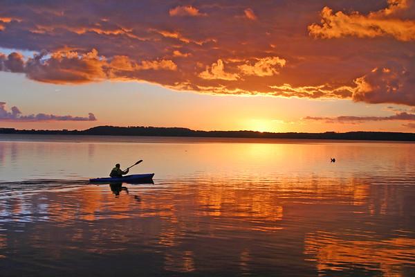 Ein Kanufahrer auf dem grossen Ploener See bei Abenddaemmerung.